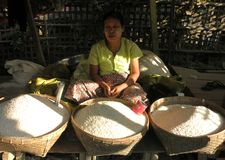 A Burmese woman with thanaka on her face selling rice stock photography