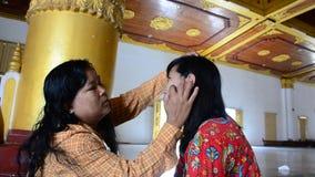 Burmese woman using thanaka makeup for traveler stock video