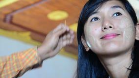 Burmese woman using thanaka makeup for traveler thai women stock video