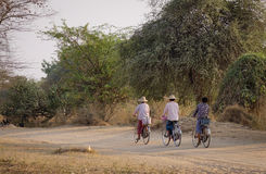 Burmese women biking on rural road in Bagan, Myanmar Royalty Free Stock Images