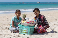 Burmese women selling fresh fruits at the shoreline to tourists in Ngapali beach. Myanmar Royalty Free Stock Image