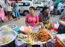 Burmese women selling sweet cakes in the market Stock Images