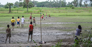 Burmese young men are playing football on rice filed in Inwa, Myanmar (Burma). Stock Photos