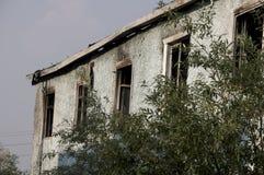 Burnеd освещает - голубое 2-storeyed здание с зелеными деревьями После пожара Стоковое Изображение