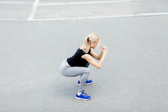 Burn in buttocks. Side view of young woman in sportswear doing squat . Young beautiful woman squats Stock Photos