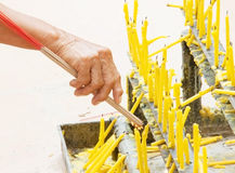 Burn incense sticks with candle and old asian hand. To show respect Stock Photo