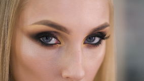 Burn look. Expressive makeup on the eyes, very pretty girl languidly looks in the frame. stock footage