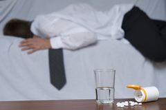 Burn out. Glass of water and pills on the table. In the background out of focus a passed out businessman on the sofa Royalty Free Stock Image