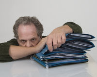 Burn Out. Man overwhelmed with work with a pile with files Stock Photo