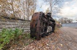 Burn-out rouillé SUV de son côté Près de la barrière concrète sur le fond des arbres et des feuilles tombées Photos libres de droits