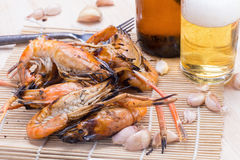 Burn shrim and Seafood sauce with beer on wooden table. Royalty Free Stock Images
