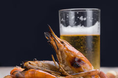 Burn shrim and Seafood sauce with beer on wooden table. Royalty Free Stock Image