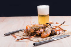 Burn shrim and Seafood sauce with beer on wooden table. Stock Photography