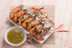 Burn shrim and Seafood sauce on wooden table. Royalty Free Stock Images