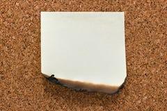 Burn sticky note on cork Stock Image