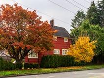 BURNABY KANADA - Oktober 24, 2018: Hus i bostadsområde med gula och röda träd i höst arkivbilder