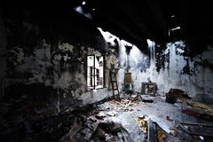 Burned abandoned room with light from the window. Stock Image