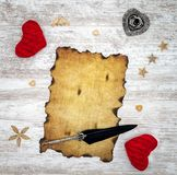 Blank burned vintage Valentine`s Day card with red cuddle hearts, wooden decorations, ink and quill - top view royalty free stock photo