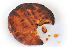 Burned biscuit. A burned, half-eaten biscuit, with a few crumbs, on a white background Royalty Free Stock Photo