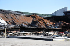 Burned Building. A burned out building with a collapsed roof against a bright blue sky Royalty Free Stock Photos