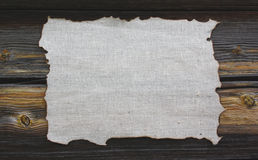 Burned canvas on a wooden background. In day Stock Image