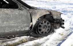 Burned Car. A view of the front portion of a car burned in fire, on a snowy landscape Stock Images