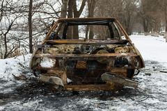 Burned car after a fire happened in winter park. Royalty Free Stock Photo