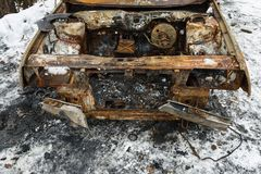 Burned car after a fire happened in winter park. Royalty Free Stock Image