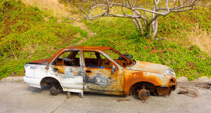 A burned car left to rot in the tropics Stock Photos
