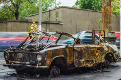 Burned Car On Road With Car Traffic On A Background Royalty Free Stock Images