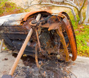 A burned car propped on its side in the caribbean Royalty Free Stock Photos