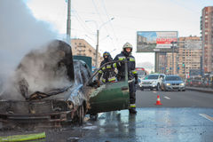 Burned car with smoke on city street Stock Photography