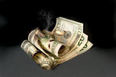 Burned cash. A smoldering pile of cash after it was burned stock images
