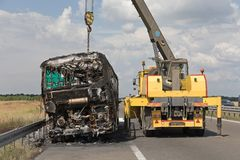 Crane Recovery Coach. Burned Coach Bus Highway Recovery Assistance royalty free stock photography