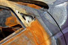Burned and corroding car. A close shot of the burned and rusty door of a passenger car Stock Images