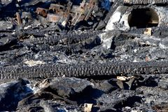 Burned debri on the ground from recent fire. Roofing materials burned and fallen to the ground amongst the debri from napa valley wildfire. Structure burned in Stock Image