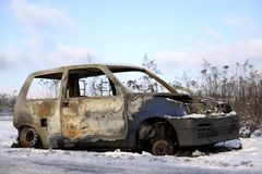 Burned, destroyed car standing on the side of the road in the winter. royalty free stock image