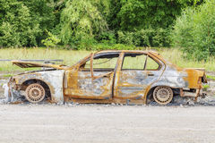 Burned down car wreck on the side of the road Stock Photography
