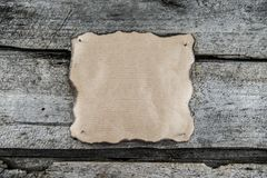 Burned edges paper background. Burned edges paper on a wood with a copy-space royalty free stock photography