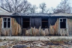 Burned by fire abandoned wooden house. Charred wall, broken windows royalty free stock photography