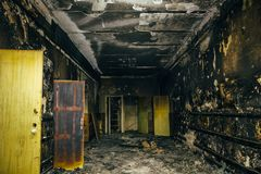 Burned by fire interior of old building. Charred ash walls, doors and damaged furniture. Dark toned royalty free stock image