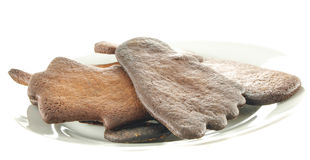 Burned gingerbread on white plate royalty free stock photography