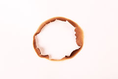 Burned hole in paper against a white background. Taken on 2014 royalty free stock image