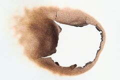 Burned hole in the paper stock photos