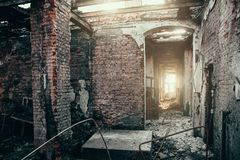 Burned house interior after fire, ruined building inside with broken brick walls. Toned royalty free stock images