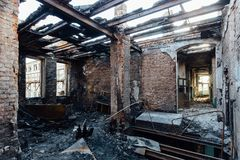 Burned interiors after fire in industrial or office building. Burnt furniture, failed roof.  stock image