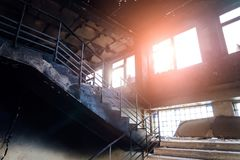Burned interiors after fire in industrial or office building. Walls and staircase in black soot.  royalty free stock photography