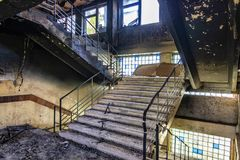 Burned interiors after fire in industrial or office building. Walls and staircase in black soot.  royalty free stock images