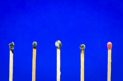 Burned match setting on blue background for ideas and inspiratio Royalty Free Stock Photos