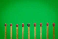 Burned match setting on green background for ideas and inspirati Royalty Free Stock Photos